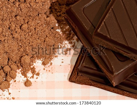 Close up detail view of a small pile of dark organic chocolate squares bars and cocoa powder on a kitchen table with checked table cloth. Desert cooking sweet food ingredients. - stock photo