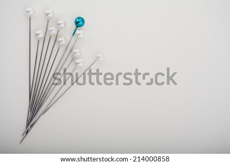 Close up detail view of a variety of a sewing pins and needles standing against a white background in a dressmaking fashion interior. Still life of a blue pin standing out from the rest.  - stock photo