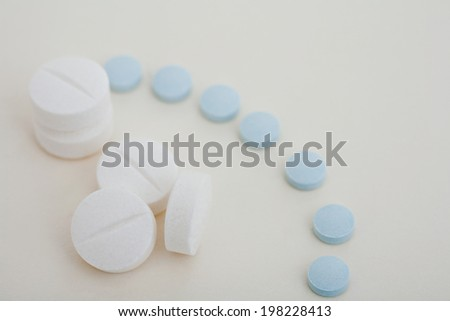 Close up detail view of a variety of different blue and white medicine pills and capsules laying on a white background table. Medicines and prescription treatments, simple background detail.