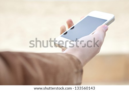 Close up detail view of a woman's hand holding a modern smart phone with a blank screen against a neutral background.