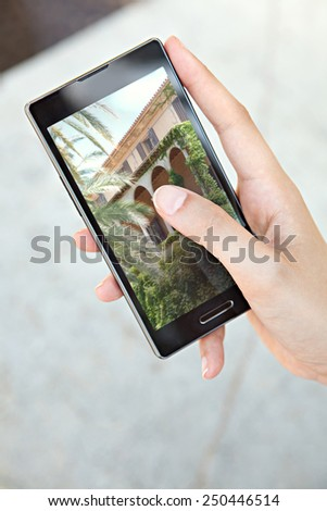 Close up detail view of a young tourist woman hands holding and using a touch screen smartphone mobile cell device, flicking through holiday pictures on vacation. Travel and lifestyle technology. - stock photo