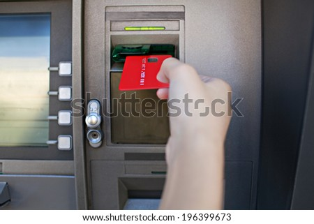 Close up detail view of a young woman hand holding and inserting a red credit card in a cash point machine with a reflective screen, outdoors. Finances and money availability funds.
