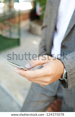 Close up detail view of an elegant businessman hand holding and using a smart phone outdoors. - stock photo
