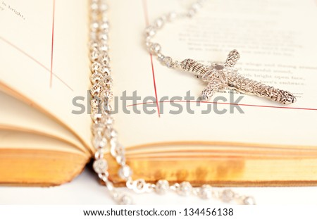 Close up detail view of an open Bible book with a silver rosary with beads and cross laying between the pages on a white desk. - stock photo