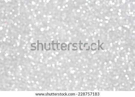 Close up detail view of silver glitter background shining and reflecting light with stars in a soft blurred view. Glitter texture. Party, celebration, abstract and festive background textures.