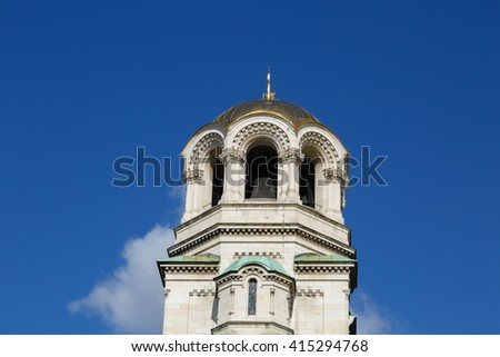 Close up detailed bellfry tower view of famous Bulgarian Orthodox church of Alexander Nevsky Cathedral built in 1882 in Sofia, Bulgaria, on blue sky background. - stock photo