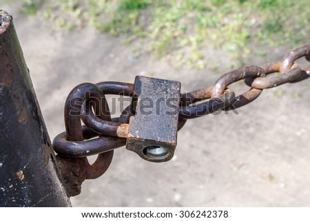 Close up detailed front view of rusty padlock, locked with chain. - stock photo