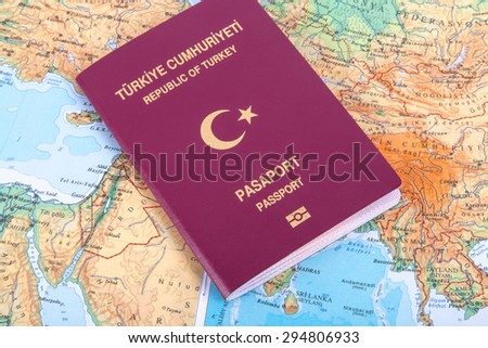Close up detailed view of a Turkish passport lying on a world map, with Republic of Turkey and Passport text in turkish.