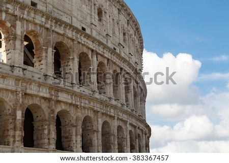 Close up detailed view of ancient amphitheatre of Colosseum built by Vespasian and Titus in Rome, on cloudy sky background.