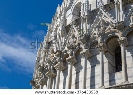 Close up detailed view of Baptisery building in Cathedral Square in Pisa, Italy, on cloudy blue sky background. - stock photo