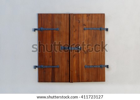 Close up detailed view of old wooden door on a white wall.