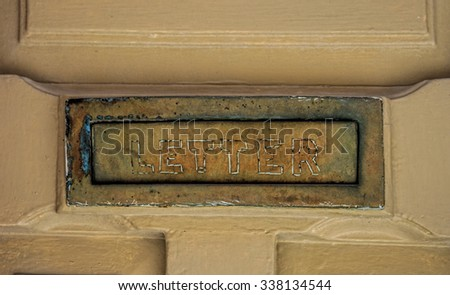 Close-up details of an aged letter post sign on a door.   - stock photo