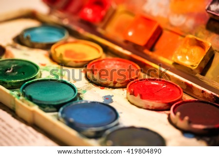 Close up diagonal view of a messy watercolor palette with colorful splatters and stains - stock photo