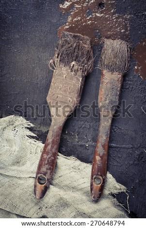 Close up dirty brushes on dark wood background - stock photo