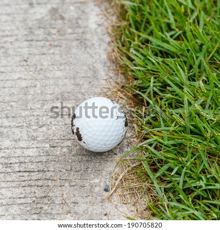 Close up dirty golf ball on the cart path - stock photo