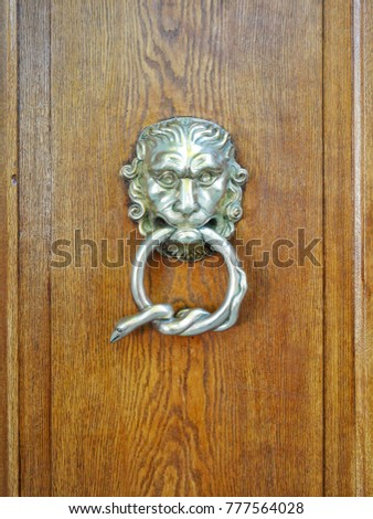 Close up door knocker on wood background,it has detail golden and design to lion with handle is circle ring in mouth
