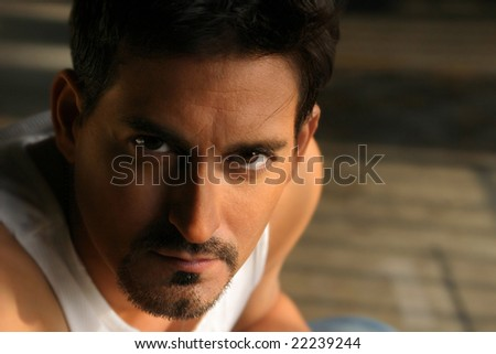 Close-up dramatic portrait of menacing man in white tank top