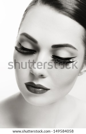 Close-up duotone portrait of young beautiful woman with eyeliner - stock photo