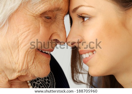Close-up. Elderly woman and beautiful granddaughter with wide smile - stock photo
