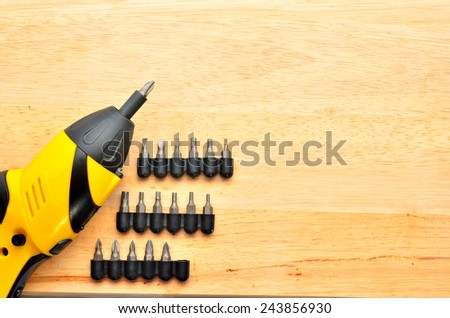 Close up electric screw driver on wooden floor - stock photo