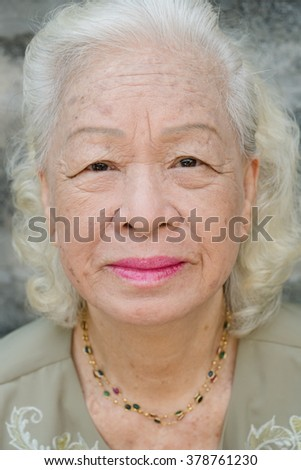 Close-up Elegant elderly woman face pink lip and whit hair , shallow dof