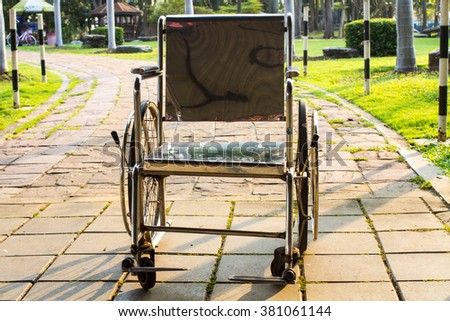 Close-up Empty wheelchair on path in the middle of park  - stock photo