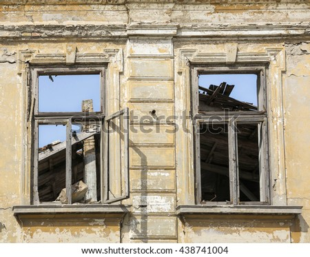 Close up - exterior facade of abandoned house with old wooden windows - stock photo