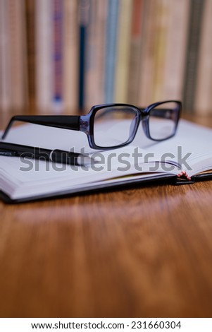 Close up Eyeglasses and Black Ballpoint Pen on Top of Open Notebook at the Wooden Office Table. - stock photo