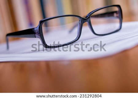 Close up Eyeglasses with Black Frame on Top of White Papers at the Wooden Table at the Office.