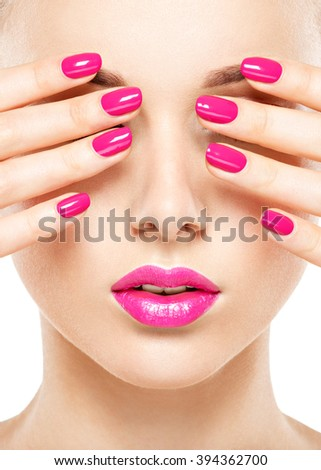 Close-up face of a beautiful  girl with bright pink  nails and lips.