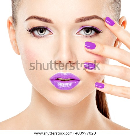 Close-up face of a beautiful  girl with purple eye makeup and bright pink  nails. Fashion model posing on white background
