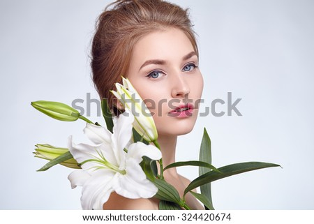 Close-up face of a girl with a flower in her hand.