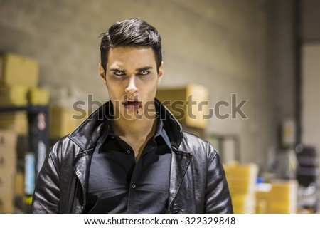 Close up Face of a Handsome Vampire Man in Leather Clothing, with Blood on his Mouth, Looking at the Camera. - stock photo