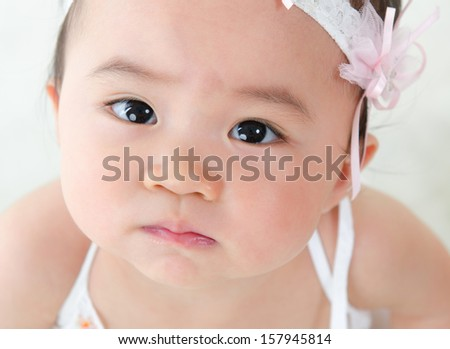 Close up face of Asian baby girl with curious look - stock photo