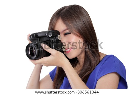 Close up face of beautiful Asian girl taking a picture using digital camera, aiming with one eye, isolated on white background - stock photo