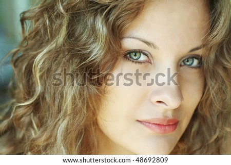 Close-up face of beautiful caucasian blonde woman with green eyes in location - stock photo