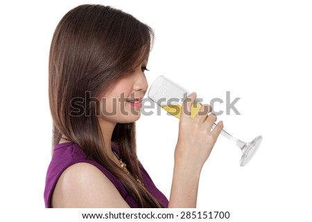 Close up face of beautiful young Asian woman drinking a glass of champagne, isolated on white background