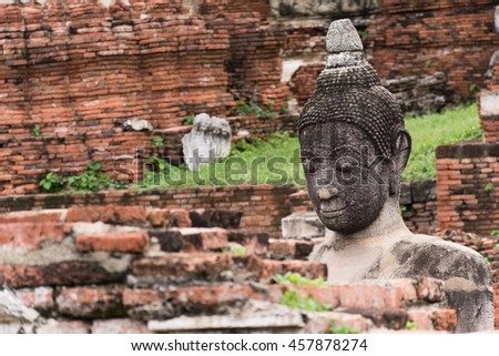 Close up face of Buddha image look through blurry focus brick wall with blurred background , Thailand. Buddha image as a symbols for Buddhist to pay respect Selective focus on buddha statue. - stock photo