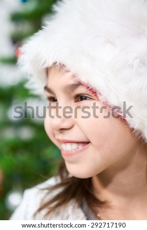 Close up face of cheerful Caucasian girl in white fur Santa hut - stock photo
