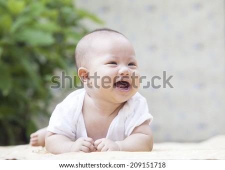 close up face of smiling baby lying on soft bed at home terrace use for infant and newborn,kid and motherhood topic  - stock photo