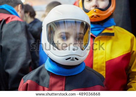 Close-up face of teenage girl and woman behind her dressed in colourful suits and helmets.