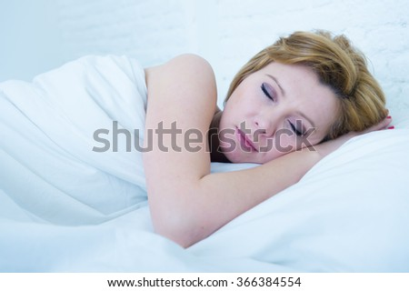 close up face of young attractive woman with red hair sleeping peacefully lying in bed at home resting and dreaming in dim night lighting set - stock photo