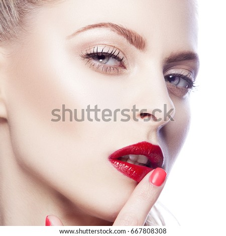 Close-up face of young woman touching her sexy red lips. Perfect skin, bright make-up. White background