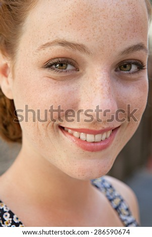 Close up face portrait of a young attractive tourist woman visiting a destination city while on a summer holiday, looking at camera and joyfully smiling, outdoors. Beauty and well being, exterior.