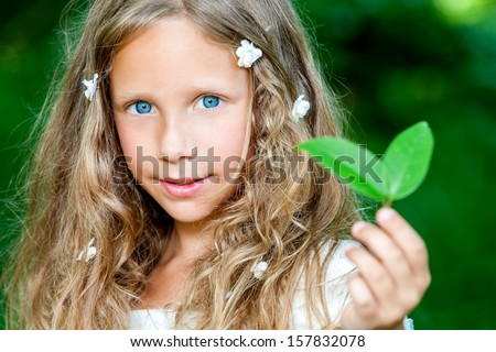 Close up face portrait of attractive girl holding green leaf outdoors.