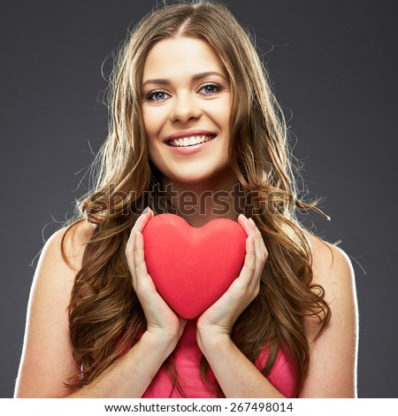 Close up face portrait of smiling woman holding red heart. Female model with long hair.