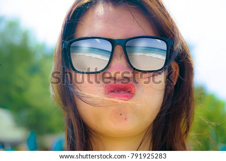 close up face portrait of young beautiful Asian woman gesturing playful wearing sunglasses with tropical beach sea and sand reflection on the glasses in travel vacation and holidays concept