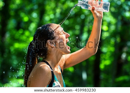 Close up face shot of female runner pouring water on face after workout. Cold water from bottle splashing on girls face against green background.