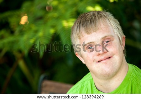 Close up face shot of friendly handicapped boy outdoors.