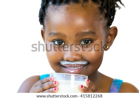 Close up face shot of sweet african girl with milk mustache.Girl holding glass of milk isolated on white background. - stock photo